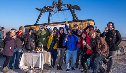 Royal Balloon passengers are celebrating landing ceremony with champagne and gold medal after the balloon tour